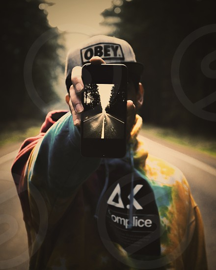 man in gray and black obey snapback holding black iphone 5 photo