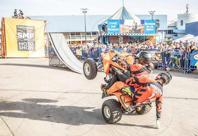 Doing Acrobatics With Quad Bike Terrain Vehicle In Front Of Crowd photo