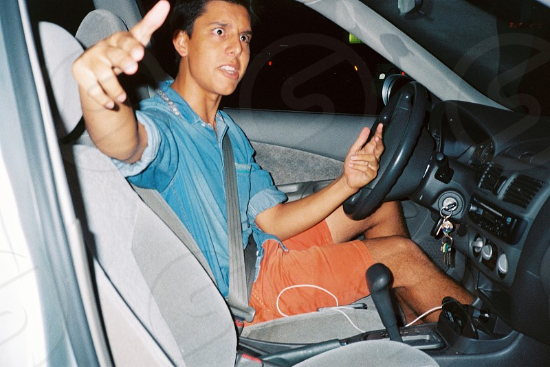 man wearing orange shorts and blue collared shirt sitting in driver's seat of automobile photo