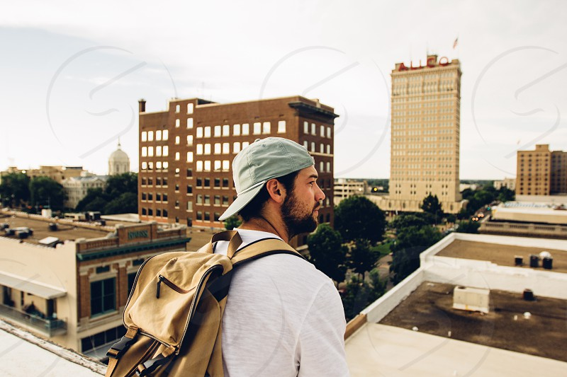 man in white shirt with brown backpack and grey fitted cap on high rise building facing brown and beige concrete building photo