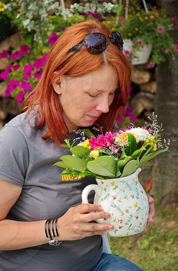 Portrait of woman with colorful flowers in vase photo