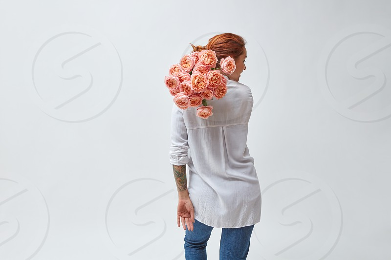A woman in jeans and a tattoo on her arms holding a bouquet of pink media roses on her shoulder mother's day valentine's day photo