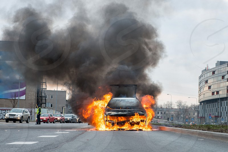 A few minutes in the street burnt car. Traffic is stopped. Firefighters eliminate fire. photo