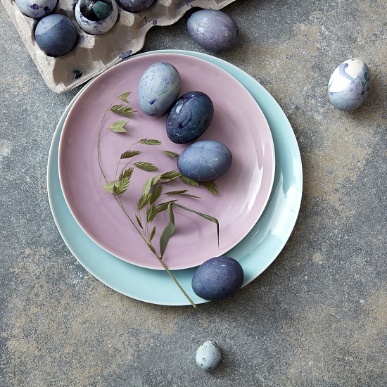 home painted eggs on a plate with leaves and a paper tray on a concrete background photo