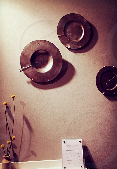 three round brown plates and forks wall decors photo