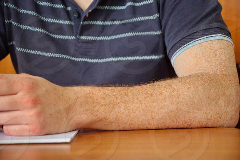 Closeup of the man's hand with freckles. Young man holding pen and making notes photo