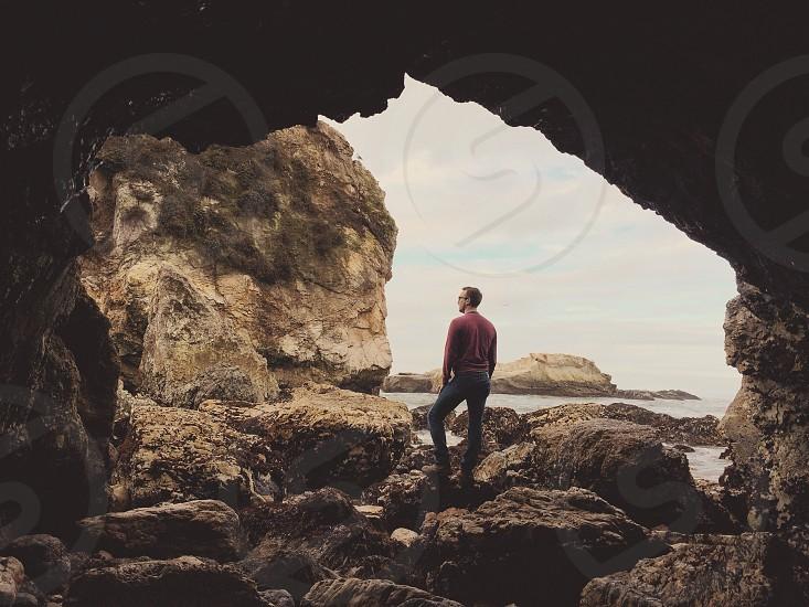 man standing on rock wearing red jacket photo
