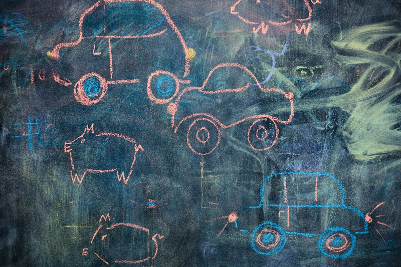 Childish colorful chalks drawings on blackboard depicting cars and characters photo