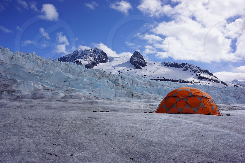 orange and grey camping tent on snow covered mountain during daytime photo