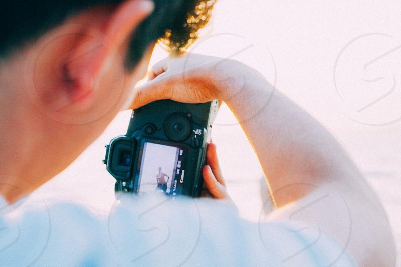 man taking photo using black dslr camera photo