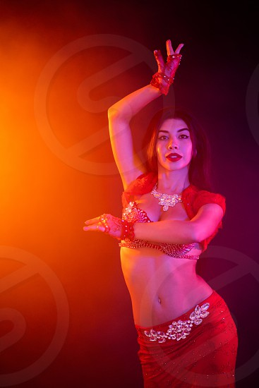 Woman in exotic costume sexually moves semi-nude body. Sexy traditional oriental belly dancer girl dancing on blue neon wall. Muslims temptation concept. Spectacular show photo