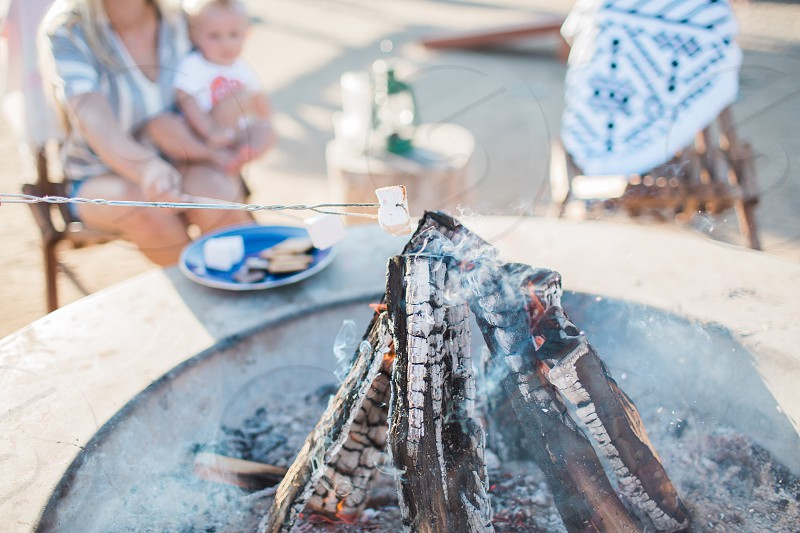 person cooking marshmallow on bonfire during daytime photo