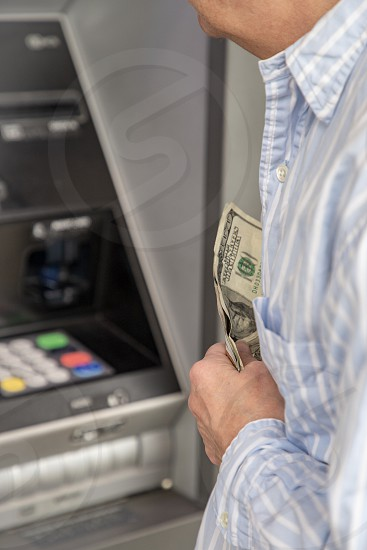Person with cash in hand at bank machine photo