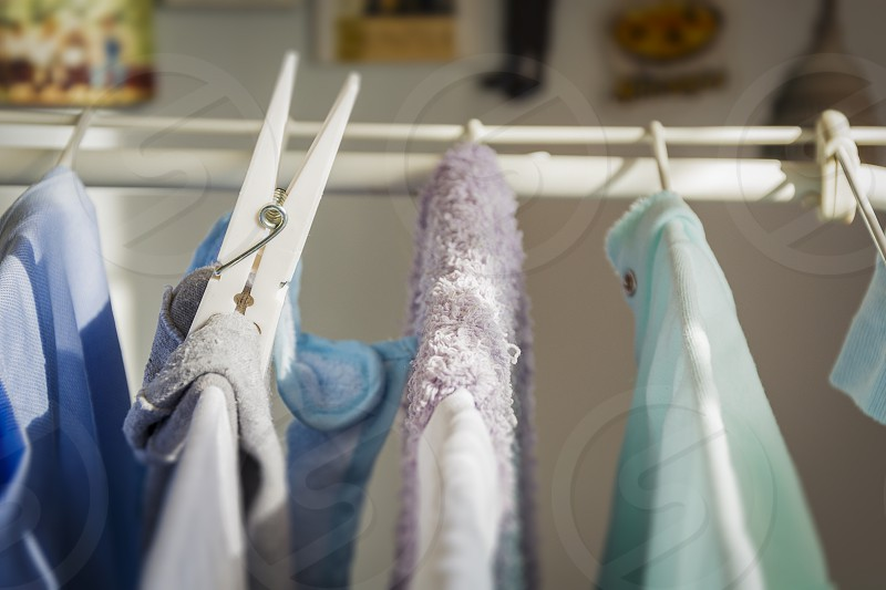 Close up of a white plastic clothespin on a clotheshorse with laundry drying photo