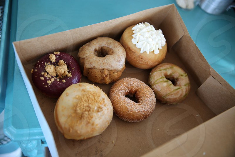 brown doughnuts with toppings on white cardboard box photo