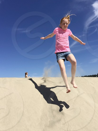 Child jumping in sand with shadow photo
