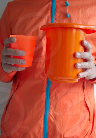 Man in orange clothes with orange cup and container photo