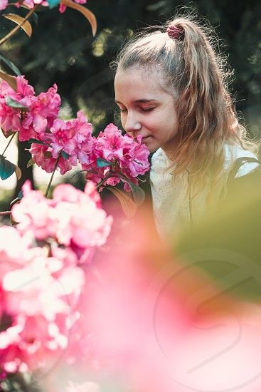 Girl with closed eyes standing in garden among the flowers smelling beautiful pink flower photo