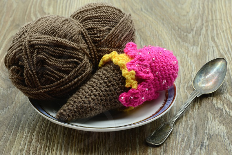 crochet ice cream cone on plate with wool and soon. Table background photo