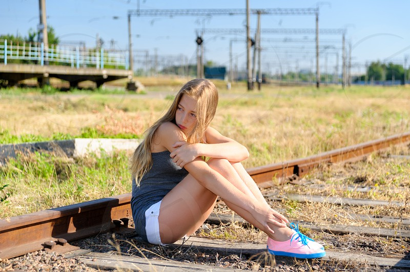 Lonely and sad teenager girl sitting on rusty rail track in the countryside. Adolescence problems photo