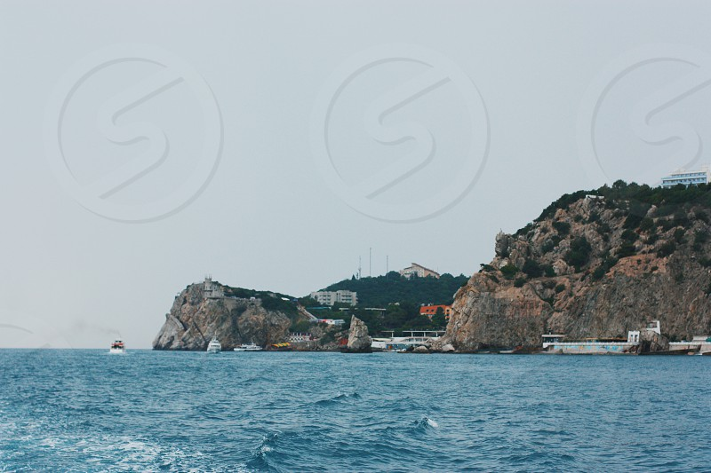 white buildings on rocky cliff shore photo