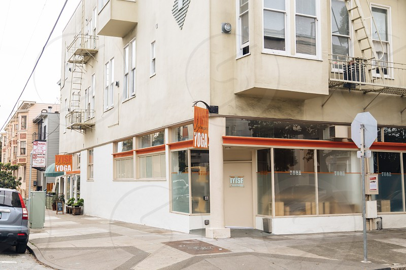 orange signage hanged on wall of white painted building during daytime photo