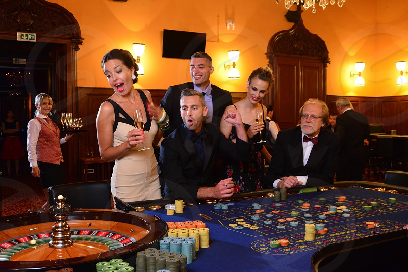 a group of people gambling at the roulette in a casino by Rino Gropuzzo.  Photo stock - Snapwire