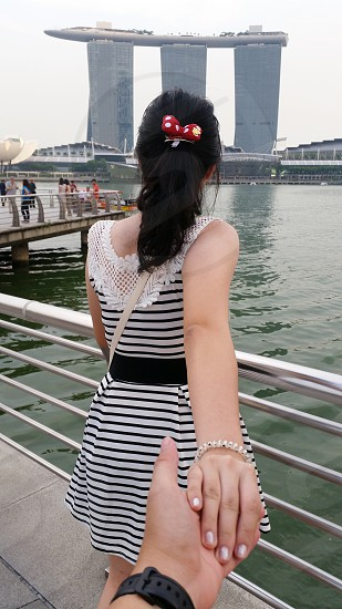 woman in white and black stripes holding the hand of person in black wristwatch beside railings near body of water photo