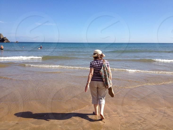 person walking by the sea shore photo