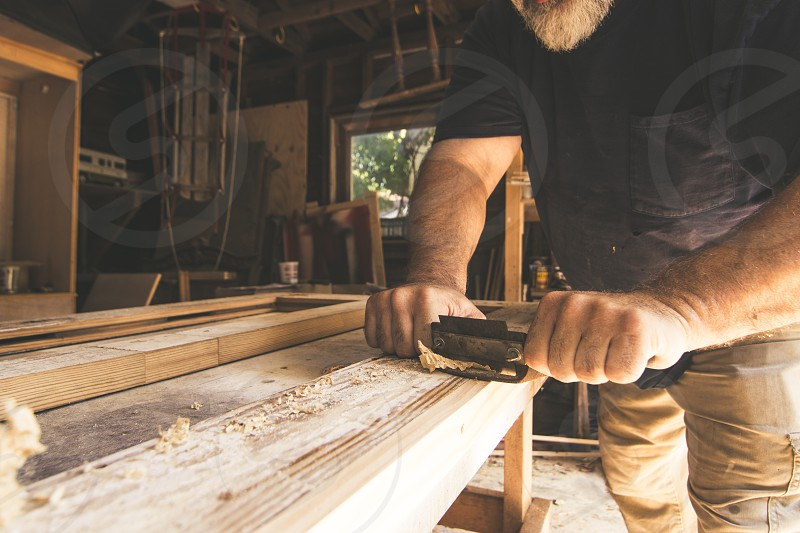 A man repairing a door in an old home using vintage tools. photo
