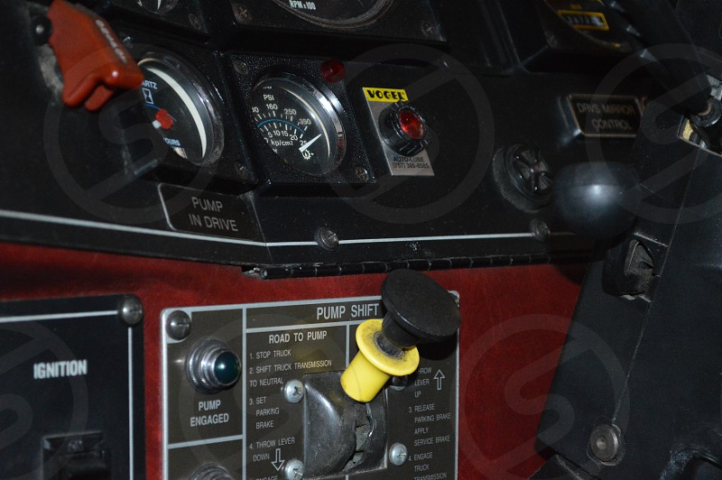 red and black control panel with gauges and push button photo