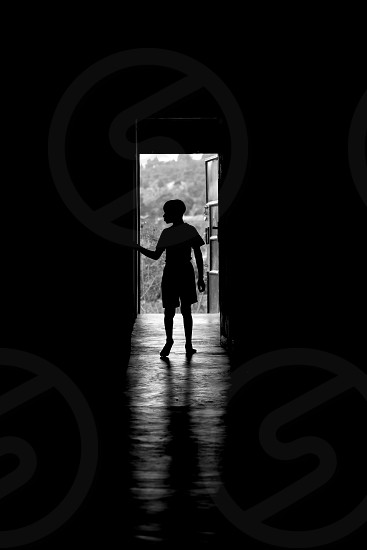 Boy standing in the doorway on his way out into the world going far away from the childrens home he lives in photo