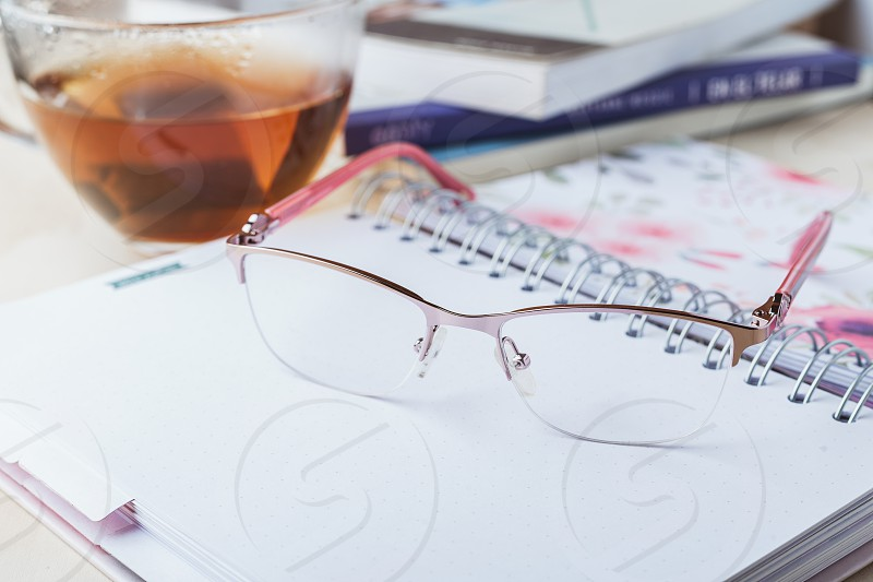 Woman glasses with notebook tea and books photo