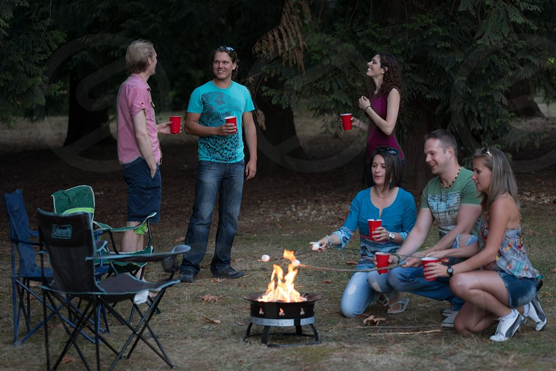 Group of adults at a campfire socializing photo