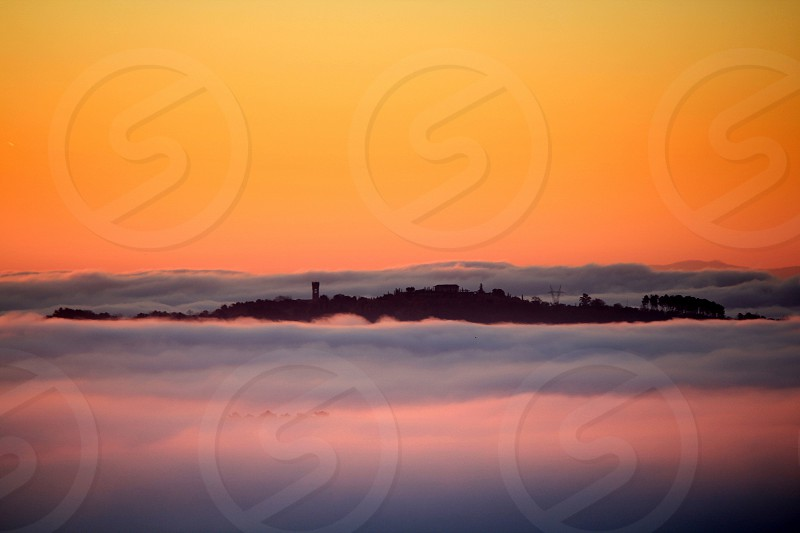 An old village above a sea of fog in the sunset photo