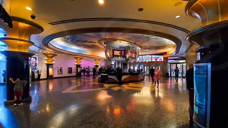 Movie theater interior lit with neon lights near Box office in the center photo