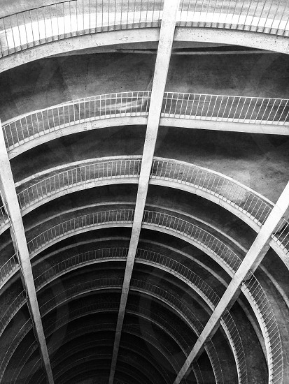 Spiral road descending perspective black and white architecture man made photo