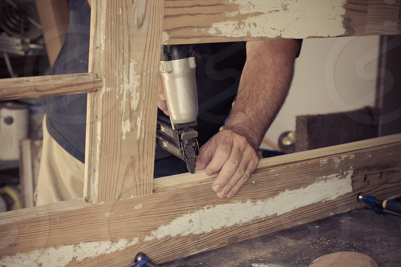 A man repairing a door for his home using a nail gun to attach molding. photo