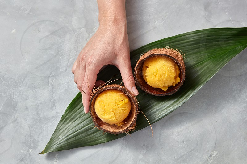 Homemade fruit ice cream in a coconut shell on a palm leaf on a gray concrete background. A girl's hand takes a shell with ice cream. Copy space for your text. Top view photo