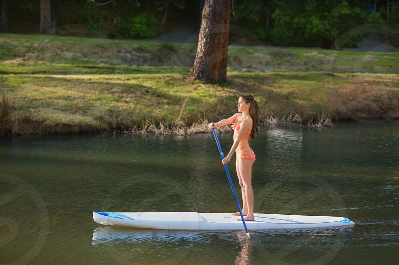 Young woman paddle boarding on a small mountain lake.  photo