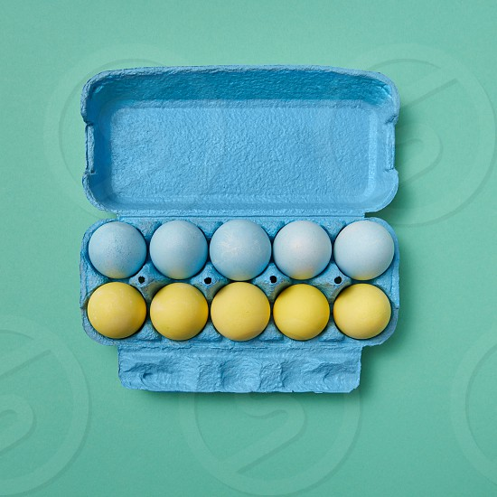 Colored yellow blue Easter eggs in a blue cardboard box on a green background with copy space. Easter layout. Flat lay photo
