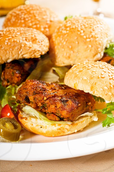 four fresh and delicious mini chicken burgers on a plate close up photo