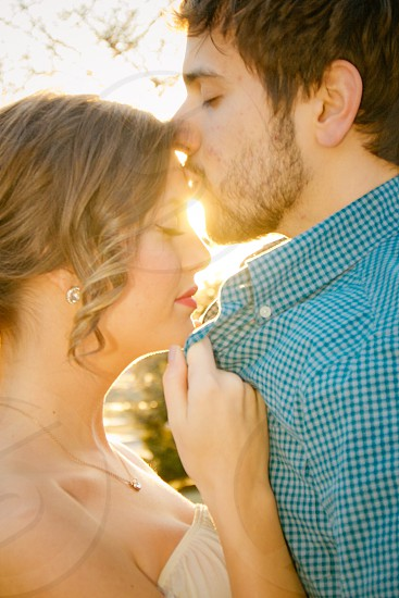 man kissing woman's forehead with eyes closed photo