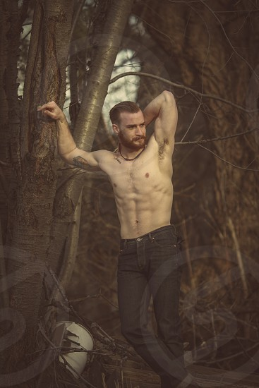 Male model muscles six pack abs hipster mustache tattoo jeans woods vintage classic handsome poise photo