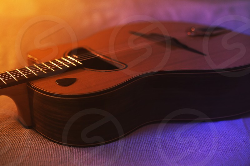 Details of a gypsy jazz acoustic guitar on bed.  photo