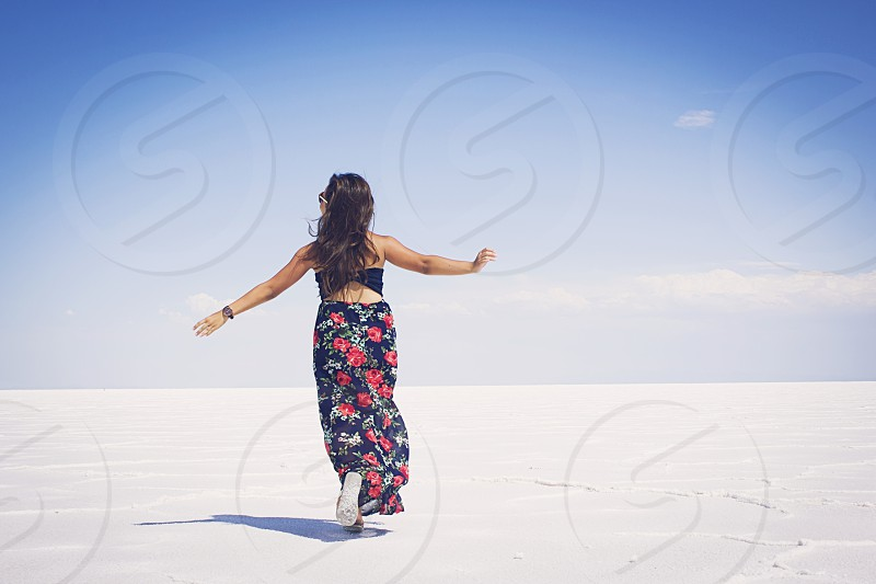 woman in red and black floral skirt running on white salt bed under clear blue sky photo