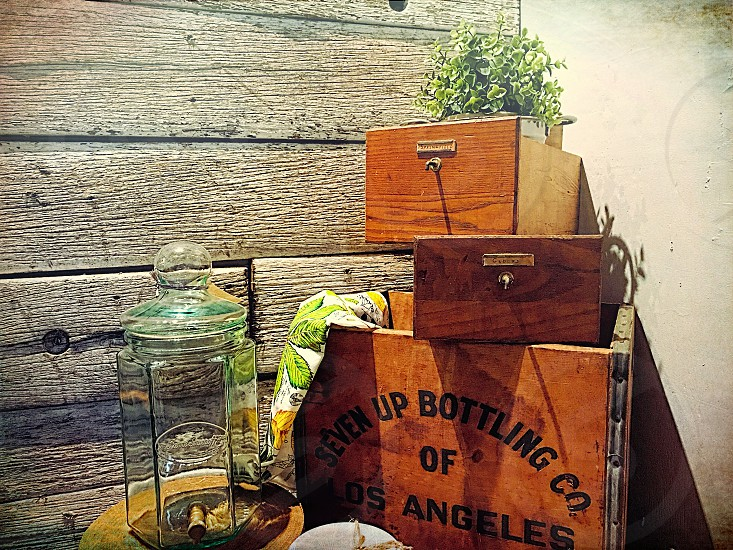 Three wooden boxes and glass jar against a wooden boarded wall photo