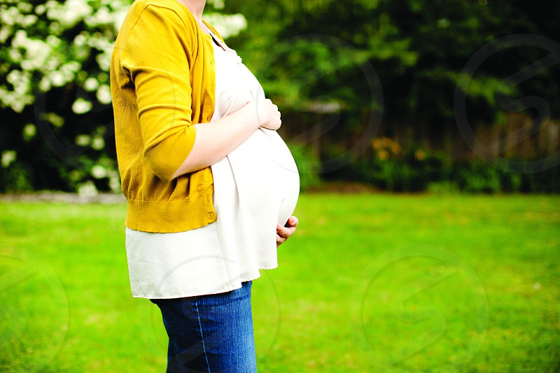 pregnant belly with yellow shirt and jeans photo
