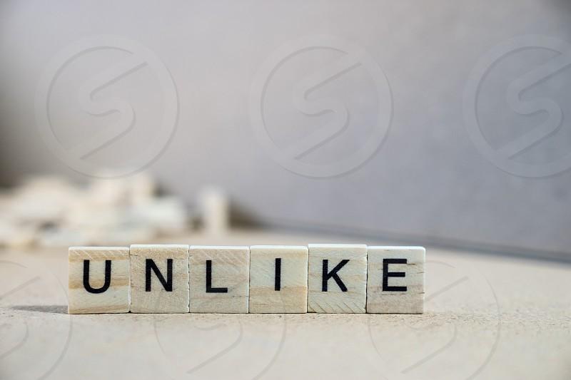 unlike word written on wood block photo