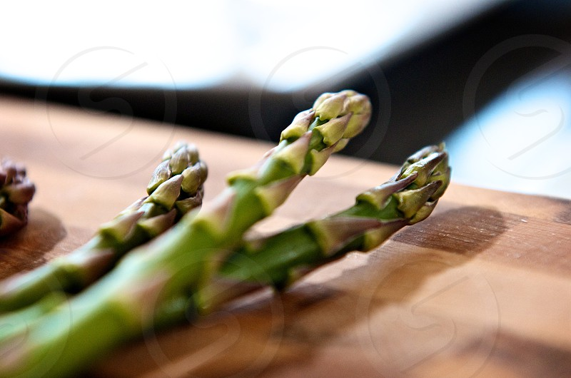 Fresh raw green asparagus on a wooden cutting board  photo